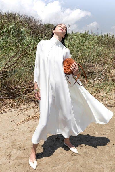 البساطة في التصميم واللون يضفيان قيمة جمالية خصوصاً مع الفستان الأبيض بقصته الواسعة المتناغمة مع الجسم