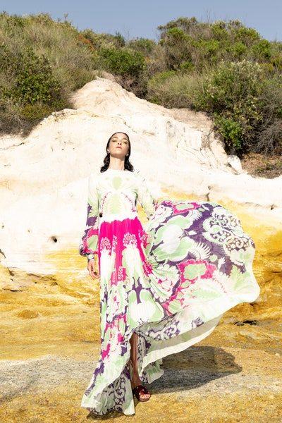 لحيوية ملفتة في هذا الصيف ومع نعومة ملفتة في الإطلالة، اختاري الفستان الطويل باللون الابيض والمزين عند الاسفل بنقشات ملونة جريئة مستوحاة من الطبيعة.