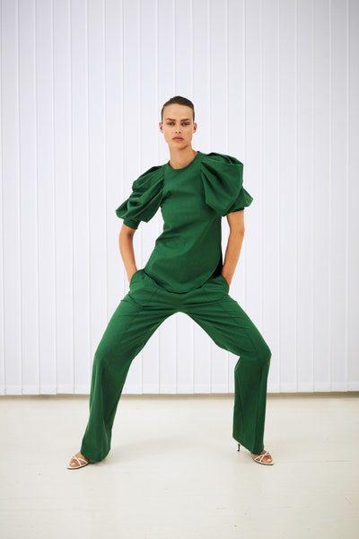 اللون الأخضر الملفت والحيوي يضفي التميز إلى هذا الزي المؤلف من السروال الكلاسيكي مع البلوزة ذات الأكمام القصيرة والمنتفخة.