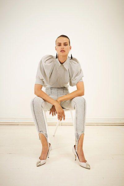 سروال باللون الرمادي الفاتح منسق مع البلوزة الرمادية ذات الاكمام المنتفخة المزينة بتقليمات بيضاء متموجة.