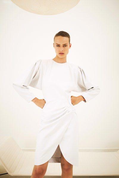 كوني انيقة ومتميزة في إطلالتك مع الفستان الميدي باللون الأبيض الذي تميّزه الاكمام المنتفخة الواسعة والشق الامامي العريض.