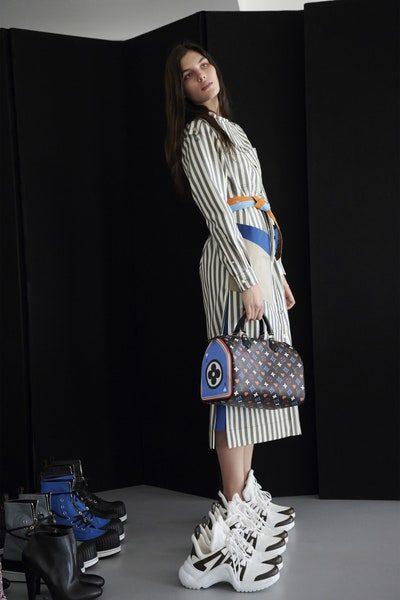 <p>فستان ذات طول ميدي باللون الابيض مقلّم بخطوط سوداء، نسّقت معه أحزمة جلدية رفيعة ملوّنة، بالاضافة الى الحذاء الرياضي ذات الحجم الضخم.</p>
