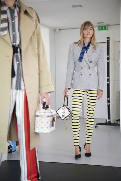 <p>ليغينغ مقلّم نسّقته الدار مع جاكيت بليزر رمادية ووشاح ازرق. واللافت حقيبة اليد العصرية التي حملتها العارضة وهي تأتي بشكل مرّبع.</p>