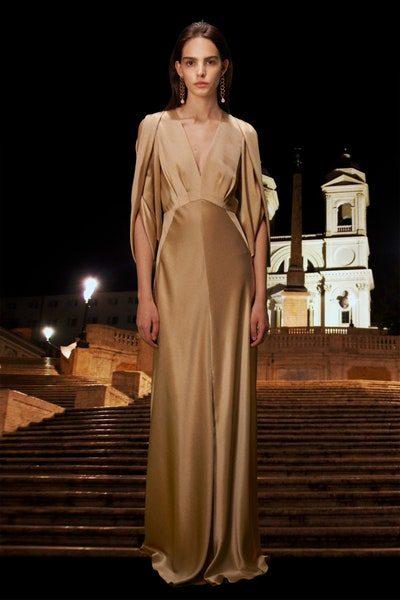 إطلالة ملكية تمتّعي بها مع هذا الفستان الطويل المصمم من القماش الذهبي اللماع، مع الأكمام بقصة الكاب وينسدل بسلاسة مع الجسم.