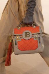 <p><strong>بالمين – Balmain</strong></p> <p>حقيبة يد صغيرة ذات شكل مربّع تتميّز بلونيها البرتقالي والرمادي. يزينها عند الجهة الأمامية حرف ب باللاتينية نسبة الى اسم الدار.</p>