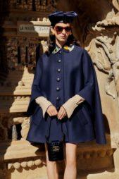 انوثة بارزة مع هذا المعطف القصير الواسع بقصة الكاب. يميّزه لونه الكحلي الدافئ تجمّله الياقة العالية بنقشاتها الملونة الحيوية.