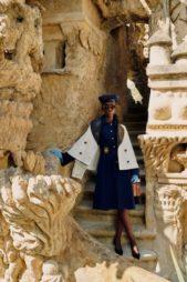 فستان ميدي كحلي اللون بقصة كلوش ريترو، تجمّله الأزرار الكبيرة الذهبية اللون. مع الحزام من اللون عينه عند الخصر. ونسقت معه الجاكيت الطويلة البيضاء مع الياقة الجلدية السوداء.