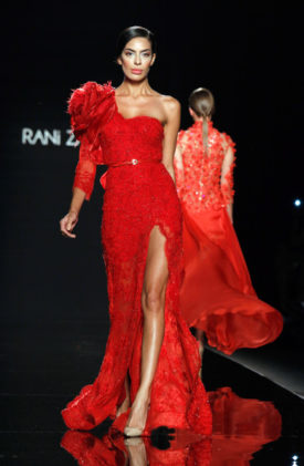 كتف مكشوف وآخر مزين بوردة حمراء كبيرة لفستان أحمر طويل وأنيق